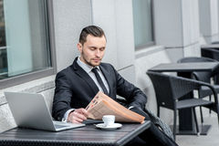 Break for lunch. Handsome businessman with beard reading a newsp Royalty Free Stock Image