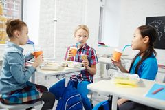 Break for lunch. Three primary school classmates eating their lunch by desks and drinking from plastic glasses Stock Photography