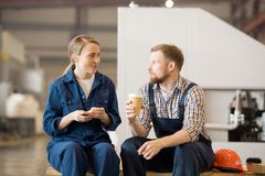 Break for lunch. Young men and women in workwear sitting in workshop while having food and drinks and talking at break stock photography