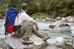 Break in the mountains. Hiker with backpack resting at a mountain river stock photo