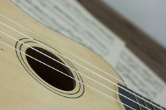 A Break From The Music. Close up of a ukulele rested on sheet music Royalty Free Stock Images