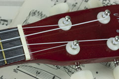 A Break From The Music. Close up of a ukulele rested on sheet music Stock Images