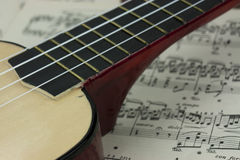 A Break From The Music. Close up of a ukulele rested on sheet music Royalty Free Stock Photo