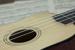 A Break From The Music. Close up of a ukulele rested on sheet music Stock Photo