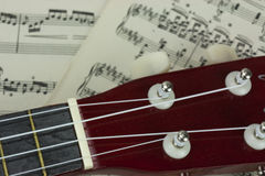 A Break From The Music. Close up of a ukulele rested on sheet music Stock Photography