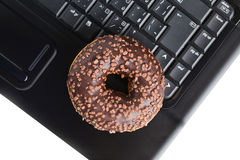 Break in the  office . doughnut on laptop keyboard Royalty Free Stock Photo