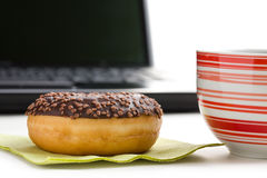 Break in the  office . doughnut on laptop keyboard Stock Images