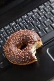 Break in the  office . doughnut on laptop keyboard Stock Image