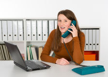 Break in the office. Young woman is calling in the office stock image