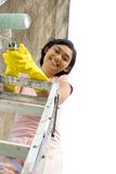 Break on painting. Portrait of cheerful asian young woman with a roller and gloves on hands standing on a ladder, taking a break during painting exterior wall of stock images