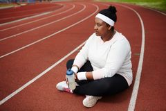 Break on race track. Young restful woman in sweatshirt, leggins and headband holding bottle of water and having break between workouts Stock Images