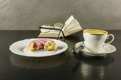 In the break of reading the book, it`s time for something sweet. Time for something sweet and drink in a break reading a book. So a cup of hot coffee and a cake Royalty Free Stock Photos