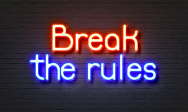Break the rules neon sign on brick wall background. Stock Image