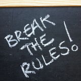 Break The Rules!. The phrase Break The Rules written by hand on a slate blackboard using white chalk Royalty Free Stock Photos