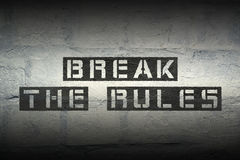 Break the rules. Stencil print on the grunge brick wall with gradient effect Stock Image