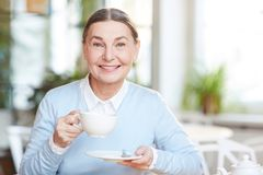Break for tea. Pretty senior female with cup of tea or coffee having rest or coffee-break in cafe Stock Photo