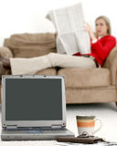 Break Time. Casual young woman taking a break from computer and bills. Focus on computer stock photo