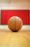 Break time. A basketball is sitting in the field with blurred red-white wall as background Royalty Free Stock Images