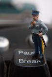 Break Time. Miniature police man eating a donut while standing on the pause/break button Stock Photo