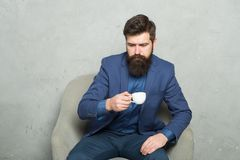 Break time. Businessman relaxing during work break at workplace. Bearded man drinking coffee during break in office stock image