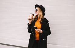 Break time! Fashion smiling woman enjoying coffee holds smartphone in city on gray. Wall background stock photos