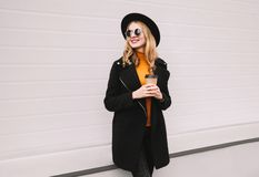 Break time! Stylish smiling young woman with coffee cup looking away in city on gray wall. Background royalty free stock images