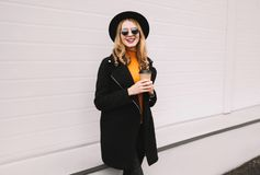 Break time! Stylish smiling young woman with coffee cup walking. In city on gray wall background royalty free stock photo
