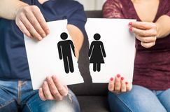 Break up, divorce and marital problems concept. Couple holding ripped pieces of paper with men and women symbol stock photos