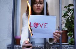 break up end of love concept. woman burning a paper with the word love stock images