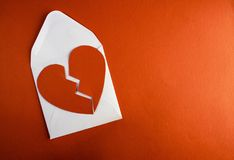 A break up envelope letter with a broken tore up paper heart. A break up valentine envelope letterwith a broken paper heart ontop of it against a red paper stock photography