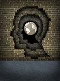 Break Through The Walls To Success. Breaking through obstacles to success with broken brick walls in the shape of a human head leading to the globe of the earth Royalty Free Stock Images