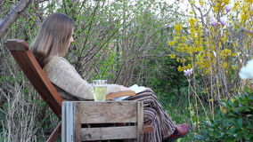 Break. A woman sitting on a lawn chair and reading a book stock video footage