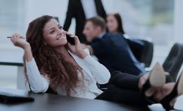 Break in work. beautiful assistant girl talking on the phone and. Close up of a girl clerk in the workplace, put my feet up on the Desk and talking on the phone Royalty Free Stock Image