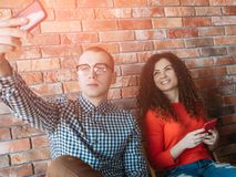 Man woman smartphones nerd selfie brunette crush. Break from work. Man and women with smartphones. Team nerd taking selfie with beautiful smiling brunette. Crush royalty free stock photo