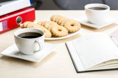 A break at work - time for something sweet. Let`s meet in the office with coffee and cookies stock photo