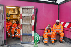 A break during work. Workers in orange robes resting on a pink background wall Royalty Free Stock Images