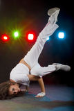 BreakDance. Female in breakdance position, standing on hands with a flying kick Stock Image
