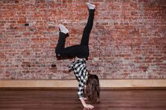 Breakdance is life. Happiness in moving. Sporty teenage girl, brick wall background with free space. Hip hop lifestyle, flexible dancing young female, movement Royalty Free Stock Photos