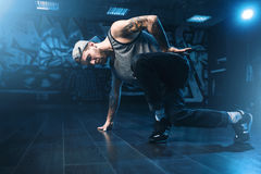 Breakdance motions, performer in dance studio. Modern urban dancing style royalty free stock images