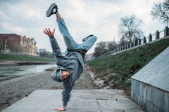 Breakdance performer, upside down motion on street. Breakdance performer, upside down motion on the street. Modern dance style. Male dancer Royalty Free Stock Image