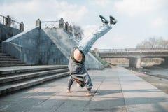 Breakdance performer, upside down motion on street. Breakdance performer, upside down motion on the street. Modern dance style. Male dancer Stock Images