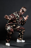 Breakdancer in camouflage. Posing against dark background Stock Images