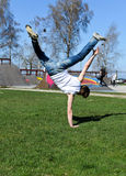 Breakdancer doing a flip. On the grass royalty free stock photo