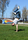Breakdancer doing a flip. On the grass Stock Image