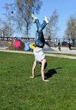 Breakdancer doing a flip. On the grass Stock Images