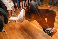 Breakdancer Midair at a Party. A breakdancer floats midair as guest watch at a party stock photography