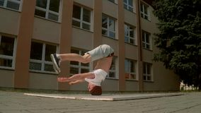 Breakdancer hace girar en su cabeza en la calle, a cámara lenta almacen de video