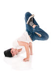 Breakdancer on lotus position. Young happy breakdancer standing upside down on head and hand with a lotus positions of the legs Stock Photo