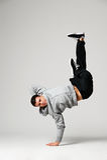 Breakdancer posing. Studio shot of breakdancer posing over grey background Stock Photo