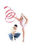 Breakdancer se pone en cuclillas y la muchacha del gimnasta con la cinta se coloca Foto de archivo libre de regalías